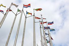 Flags of different countries on cloudy sky background Stock Photos