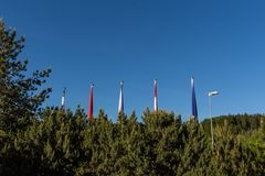 Flags of different countries on the flagpoles on the blue sky.  Royalty Free Stock Images