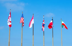 Flags of different countries on the flagpoles royalty free stock images