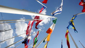 Flags of different countries flapping in sky. Many bright flags waving at blue sky background stock video footage