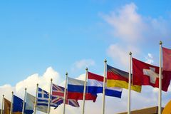 Flags of different countries flapping in wind. Against blue sky royalty free stock images