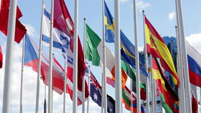 Flags of different countries flapping in wind. Many bright flags waving near modern office building in Moscow stock footage