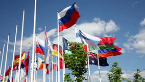 Flags of different countries flapping in wind. Many bright flags waving near modern office building in Moscow stock video