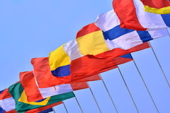 Flags of different countries. Different countries national flags getting together under blue sky, shown as worldwide, country, and international communication or Stock Images