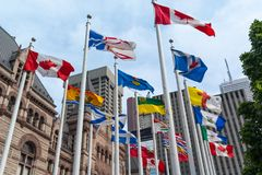 Flags of different countries waiving with wind. Flags of different countries waving with wind against of building of old city hall of Toronto, Canada Royalty Free Stock Photography