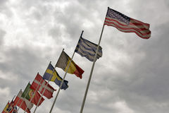 Flags of different countries waving against a cloudy sky. National flags of different countries in the row waving against a cloudy sky Royalty Free Stock Photography