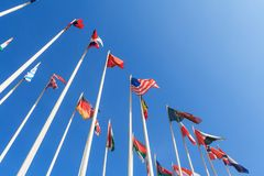 Flags of different countries of the world. Bottom view of a rows of flags of different countries of the world, flutters in the wind, against a clear blue sky royalty free stock image