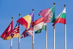 Flags of different countries of the world. Against a bright blue sky stock images