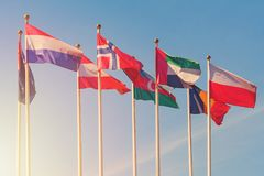 Flags of different countries of the world. Flutters in the wind against a sunlight toned stock photos