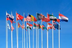 Flags of different countries of the world. Flutters in the wind a background of clear blue sky stock photo