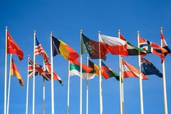 Flags of different countries of the world. Rows of a flags of different countries of the world a background of clear blue sky stock photo