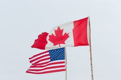 Flags of different USA and Canada on the background of the gloom. Y sky stock images