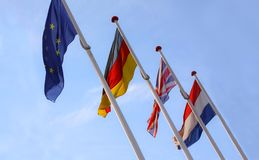 Flags from England, United Kingdom, Germany and Nederlands waving from flagpoles together with the EU, European Union, flag agains. T a blue sky - stock image stock image