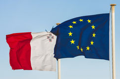 Flags of the EU and Malta. Flags of the European Union and Malta next to each other on the blue sky waving in the wind Royalty Free Stock Image