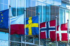 Flags of European countries. Waving flags of the European Union and four European countries - Poland, Sweden, Norway, Denmark - in front of a modern building stock photo