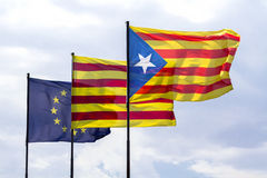 Flags of European Union and Catalonia with the Catalan secession. Three flags fluttering together on a windy day: the flag of the European Union, the ancient stock image