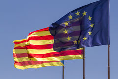 Flags of European Union and Catalonia waving together on a blue. Three flags fluttering together on a windy day: the flag of the European Union and the ancient royalty free stock images