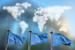 Flags of European Union with clouds map. Flags of European Union with world map made of clouds against European Parliament in Brussels, Belgium Stock Images