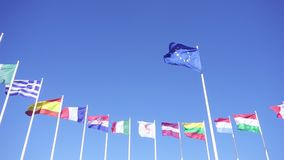 Flags of European Union countries against the blue sky. Flag of European Union with EU member flags on the background against the blue sky. Smooth slowmotion stock video