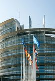 Flags of European Union countries waving before European Parliament building. Facade of the European Parliament building in Strasbourg, France with all European stock photography