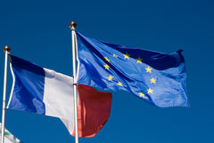 Flags of the European Union and France. Waving in the wind. Blue sky in background Royalty Free Stock Photography