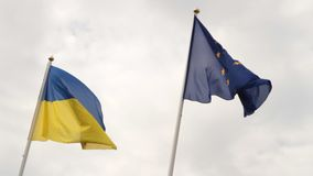 Flags of European Union and Ukraine waving on flagpoles isolated on white background stock video