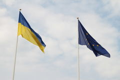 Flags of European Union and Ukraine waving on flagpoles isolated on white background.  Royalty Free Stock Photos