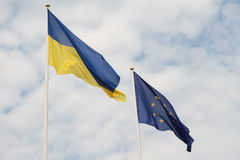 Flags of European Union and Ukraine waving on flagpoles isolated on white background.  Stock Photo