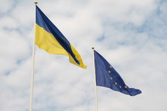 Flags of European Union and Ukraine waving on flagpoles isolated on white background.  Stock Image
