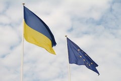 Flags of European Union and Ukraine waving on flagpoles isolated on white background.  Royalty Free Stock Images