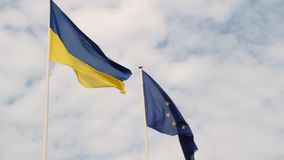 Flags of European Union and Ukraine waving on flagpoles isolated on white background. stock video footage