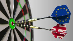 Flags of the European Union and the United Kingdom on darts hitting bullseye of the target. International cooperation or. Competition animation stock footage