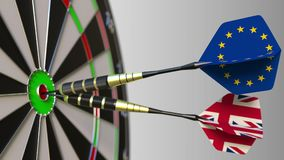 Flags of the European Union and the United Kingdom on darts hitting bullseye of the target. International cooperation or. Competition Stock Photos