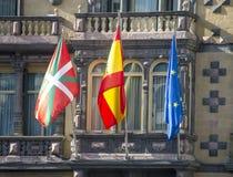 Flags of Euskadi, Spain and European Union. Waving in the facade of a building Stock Photos