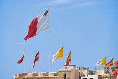 The flags flap over the fortress walls for a holiday. Malta. The flags of Malta, Sovereign Military Order of Malta, Vatican and Spain raised over the fortress Stock Photo