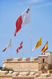 The flags flap over the fortress walls for a holiday. Malta. The flags of Malta, Sovereign Military Order of Malta, Vatican and Spain raised over the fortress Stock Image