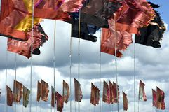 Flags fluttering in the wind. A picture of many flags hoisted up on long, thin flagpoles, fluttering in the strong winds Stock Photography