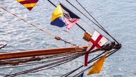 Flags fly in the wind. Flags follow along the mast. It is lowered and is at the horizontal of the boat. Photo taken near a harbor. The boat was going to park Royalty Free Stock Image
