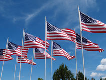 Flags Flying. Several American flags flying in a strong breeze against a beautiful blue sky at a flag memorial site in Eastlake, Ohio Stock Image