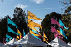 Flags flying atop carnival tents against blue sky Royalty Free Stock Photography
