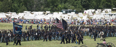 Flags flying at Gettysburg. A long line of Union soldiers take to the battlefield let by a marching band at the 150th anniversary of the battle of Gettysburg Stock Images