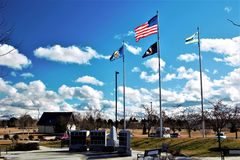 Flags flying at the Rock of Honor. In Julius M. Kliener Memorial Park Meridian, ID. Blue sky with broken clouds Royalty Free Stock Photography