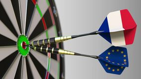 Flags of France and the European Union on darts hitting bullseye of the target. Flags of France and the European Union on darts hitting bullseye stock video footage