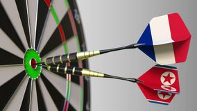 Flags of France and North Korea on darts hitting bullseye of the target. Flags of France and North Korea on darts hitting bullseye stock video footage