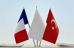 Flags of France and Turkey. Desktop flags of France and Turkey with white flag in the middle stock image