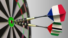 Flags of France and the UAE on darts hitting bullseye of the target. International cooperation or competition conceptual. Flags of France and the UAE on darts stock footage
