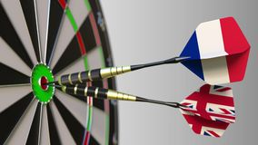 Flags of France and the United Kingdom on darts hitting bullseye of the target. International cooperation or competition. Animation stock video footage