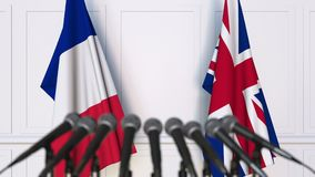 Flags of France and The United Kingdom at international meeting or negotiations press conference. 3D animation stock footage