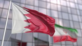 Waving flags of Bahrain and Iran in front of a modern skyscraper facade