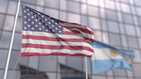 Waving flags of the USA and Argentina in front of a modern skyscraper facade
